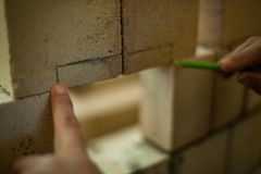 Το άτομο μετρά τα τούβλα χτίζοντας έναν τοίχο στοκ εικόνες