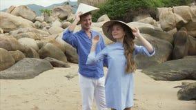 Το άτομο με ένα κορίτσι βάζει το βιετναμέζικο καπέλο στα κεφάλια, τα φιλιά και τις καλύψεις τους τα πρόσωπά τους με τα καπέλα φιλμ μικρού μήκους