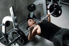 Το άτομο με ένα μυϊκό σώμα εκτελεί έναν Τύπο πάγκων χρησιμοποιώντας ένα barbell στοκ φωτογραφίες