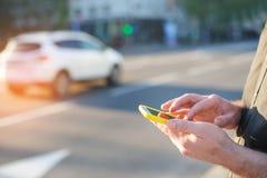 Το άτομο με ένα τηλέφωνο στο χέρι του γράφει ένα μήνυμα Στοκ εικόνες με δικαίωμα ελεύθερης χρήσης