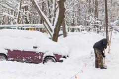 Το άτομο με ένα φτυάρι καθαρίζει το χιόνι από το δρόμο κοντά στο αυτοκίνητο στο χώρο στάθμευσης Στοκ Εικόνες
