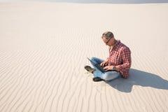 Το άτομο με ένα lap-top κάθεται μόνο στη μέση της ερήμου Στοκ φωτογραφία με δικαίωμα ελεύθερης χρήσης