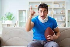 Το άτομο με το αμερικανικό ποδόσφαιρο προσοχής τραυματισμών λαιμών στο σπίτι Στοκ φωτογραφία με δικαίωμα ελεύθερης χρήσης