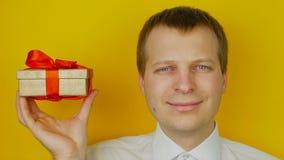 Το άτομο με το δώρο μέσα στο κιβώτιο χαμογελά και εξετάζει τη κάμερα, στο κίτρινο υπόβαθρο τοίχων απόθεμα βίντεο