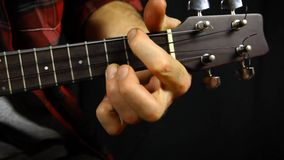 Το άτομο με το κόκκινο πουκάμισο παίζει σε ένα μικρό ukulele Κινηματογράφηση σε πρώτο πλάνο στο αριστερό χέρι απόθεμα βίντεο