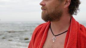 Το άτομο με μια γενειάδα και τα μπλε μάτια και ένας σταυρός στο στήθος του στα πλαίσια της θάλασσας αναπνέουν 4 Κ βίντεο φιλμ μικρού μήκους