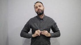Το άτομο με μια γενειάδα κουμπώνει το πουκάμισό του απόθεμα βίντεο
