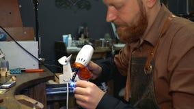 Το άτομο με μια γενειάδα κρατά μια συσκευή με τις υπεριώδεις ακτίνες για τη διαδικασία σμάλτο σε ένα ασημένιο δαχτυλίδι απόθεμα βίντεο
