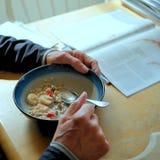 Το άτομο με παραδίδει το πρωί, τρώγοντας oatmeal προγευμάτων με τις φράουλες και τις μπανάνες στον πίνακα κουζινών του στοκ εικόνα