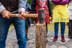Το άτομο με το σφυρί ελκήθρων παίρνει έτοιμο να χωρίσει το ξύλο στοκ εικόνες