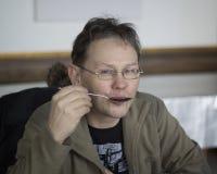 Το άτομο με τα γυαλιά κρατά στο χέρι του ένα κουτάλι σούπας Στοκ Εικόνες
