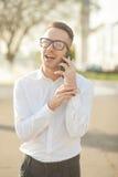 Το άτομο με τα γυαλιά μιλά στο κινητό τηλέφωνο στα χέρια Στοκ εικόνα με δικαίωμα ελεύθερης χρήσης