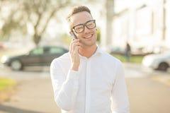 Το άτομο με τα γυαλιά μιλά στο κινητό τηλέφωνο στα χέρια Στοκ φωτογραφία με δικαίωμα ελεύθερης χρήσης