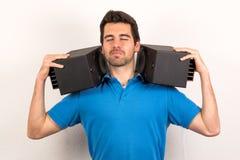 Το άτομο με τα μεγάφωνα στους ώμους του απολαμβάνει τον ήχο στοκ εικόνα