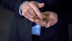 Το άτομο με τα μεσαίου εισοδήματος μετρώντας νομίσματα, χαμηλός μισθός, δαπάνες υπερβαίνει τα εισοδήματα στοκ φωτογραφίες