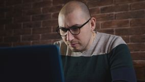 Το άτομο με τα παιχνίδια πάθους στον υπολογιστή Το άτομο στα γυαλιά που χρησιμοποιούν το lap-top φιλμ μικρού μήκους