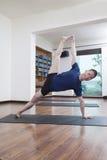 Το άτομο με τα πόδια που αυξήθηκαν και τα όπλα να κάνει τη γιόγκα σε ένα στούντιο γιόγκας Στοκ εικόνες με δικαίωμα ελεύθερης χρήσης