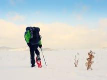 Το άτομο με τα πλέγματα σχήματος ρακέτας και το σακίδιο πλάτης παίρνουν τις φωτογραφίες από το smartphone Οδοιπόρος snowdrift Στοκ Φωτογραφία