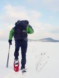 Το άτομο με τα πλέγματα σχήματος ρακέτας παίρνει ένα υπόλοιπο στο χιόνι Οδοιπόρων Στοκ φωτογραφία με δικαίωμα ελεύθερης χρήσης