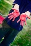 Το άτομο με τα χέρια χρωμάτισε με το κόκκινο χρώμα σωμάτων Στοκ φωτογραφία με δικαίωμα ελεύθερης χρήσης