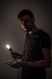 Το άτομο με τη λάμπα φωτός στο μαύρο υπόβαθρο Στοκ φωτογραφία με δικαίωμα ελεύθερης χρήσης