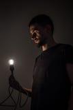 Το άτομο με τη λάμπα φωτός στο μαύρο υπόβαθρο Στοκ εικόνα με δικαίωμα ελεύθερης χρήσης