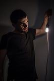 Το άτομο με τη λάμπα φωτός στο μαύρο υπόβαθρο Στοκ Φωτογραφίες