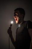 Το άτομο με τη λάμπα φωτός στο μαύρο υπόβαθρο Στοκ εικόνες με δικαίωμα ελεύθερης χρήσης