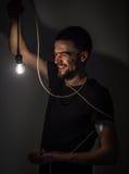 Το άτομο με τη λάμπα φωτός στο μαύρο υπόβαθρο Στοκ Εικόνα