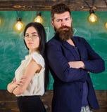 Το άτομο με τη γενειάδα και ο δάσκαλος eyeglasses στέκονται πίσω να υποστηρίξουν, πίνακας κιμωλίας στο υπόβαθρο Κυρία και hipster Στοκ φωτογραφίες με δικαίωμα ελεύθερης χρήσης