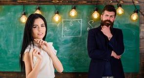 Το άτομο με τη γενειάδα και ο νέος γυναικείος δάσκαλος στέκονται στην τάξη, πίνακας κιμωλίας στο υπόβαθρο Γυναικείος δάσκαλος και Στοκ φωτογραφίες με δικαίωμα ελεύθερης χρήσης