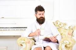 Το άτομο με τη γενειάδα και mustache απολαμβάνει το πρωί καθμένος στην πολυθρόνα πολυτέλειας Το άτομο νυσταλέο στο μπουρνούζι, πί Στοκ εικόνες με δικαίωμα ελεύθερης χρήσης