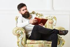 Το άτομο με τη γενειάδα και mustache κάθεται στην πολυθρόνα και το βιβλίο ανάγνωσης, άσπρο υπόβαθρο τοίχων πλήρες απομονωμένο κεφ στοκ φωτογραφία