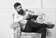 Το άτομο με τη γενειάδα και mustache κάθεται στην πολυθρόνα και το βιβλίο ανάγνωσης, άσπρο υπόβαθρο τοίχων πλήρες απομονωμένο κεφ στοκ εικόνα