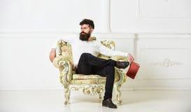 Το άτομο με τη γενειάδα και mustache κάθεται στην πολυθρόνα, κρατά το βιβλίο, άσπρο υπόβαθρο τοίχων Αντανακλάσεις στην έννοια λογ στοκ φωτογραφία με δικαίωμα ελεύθερης χρήσης