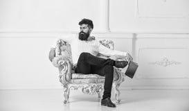 Το άτομο με τη γενειάδα και mustache κάθεται στην πολυθρόνα, κρατά το βιβλίο, άσπρο υπόβαθρο τοίχων Αντανακλάσεις στην έννοια λογ στοκ εικόνα