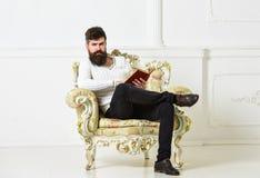 Το άτομο με τη γενειάδα και mustache κάθεται στην πολυθρόνα και την ανάγνωση, άσπρο υπόβαθρο τοίχων Ο ειδήμων, καθηγητής απολαμβά στοκ φωτογραφία με δικαίωμα ελεύθερης χρήσης