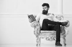 Το άτομο με τη γενειάδα και mustache κάθεται στην πολυθρόνα και την ανάγνωση, άσπρο υπόβαθρο τοίχων Ο φαλλοκράτης ξοδεύει τον ελε στοκ εικόνες με δικαίωμα ελεύθερης χρήσης