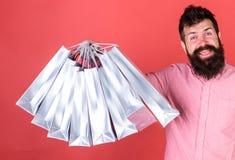 Το άτομο με τη γενειάδα και mustache κρατά τις τσάντες αγορών, κόκκινο υπόβαθρο Το Hipster στο ευτυχές πρόσωπο ψωνίζοντας εθίζει  Στοκ Φωτογραφία
