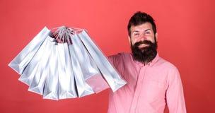 Το άτομο με τη γενειάδα και mustache κρατά τις τσάντες αγορών, κόκκινο υπόβαθρο Το Hipster στο ευτυχές πρόσωπο ψωνίζοντας εθίζει  Στοκ εικόνα με δικαίωμα ελεύθερης χρήσης