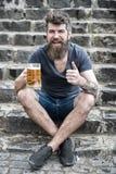Το άτομο με τη γενειάδα και mustache στο ευτυχές πρόσωπο, πετρώδες υπόβαθρο, Το γενειοφόρο άτομο κρατά την κούπα μπύρας, πίνει τη Στοκ Εικόνες