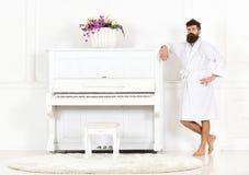 Το άτομο με τη γενειάδα στο μπουρνούζι απολαμβάνει το πρωί στεμένος κοντά στο πιάνο Ταλαντούχος έννοια μουσικών Σοβαρές στάσεις α στοκ φωτογραφία με δικαίωμα ελεύθερης χρήσης