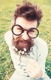 Το άτομο με τη μακριά γενειάδα και mustache, το πράσινο υπόβαθρο Hipster με τη γενειάδα στο εύθυμο πρόσωπο, που θέτει με τα γυαλι στοκ φωτογραφίες