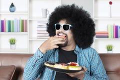 Το άτομο με τη σγουρή τρίχα τρώει donuts Στοκ φωτογραφία με δικαίωμα ελεύθερης χρήσης