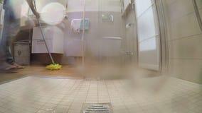 Το άτομο με τις σαγιονάρες και το παντελόνι πλένει το πάτωμα στο λουτρό όπως βλέπει από το ντους απόθεμα βίντεο