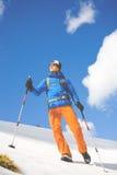 Το άτομο με τους πόλους οδοιπορίας περνά από το χιόνι στα βουνά Στοκ φωτογραφία με δικαίωμα ελεύθερης χρήσης