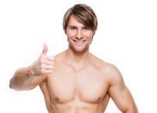 Το άτομο με το μυϊκό κορμό παρουσιάζει ότι οι αντίχειρες υπογράφουν επάνω Στοκ Εικόνες