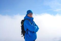Το άτομο με το σακίδιο πλάτης που φορά τα γυαλιά ηλίου στέκεται στα βουνά μέσα Στοκ εικόνα με δικαίωμα ελεύθερης χρήσης