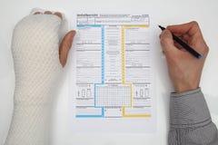 Το άτομο με το συνδεδεμένο χέρι συμπληρώνει μια έκθεση ατυχήματος Στοκ Εικόνες