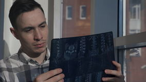 Το άτομο με το mustache στο παράθυρο βλέπει την εικόνα ακτίνας X της σπονδυλικής στήλης απόθεμα βίντεο